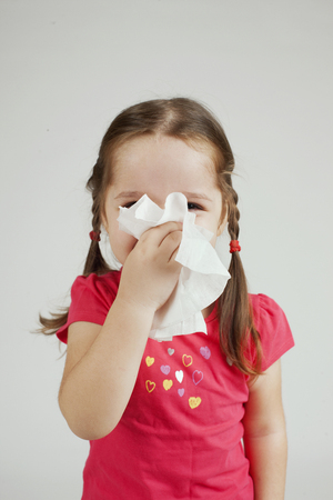 holding nose: Little girl wipes her nose with a tissue.