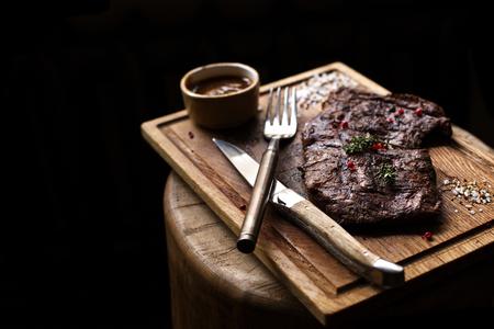 牛肉のステーキ。コピー スペースで大まかな木製机の上スパイスと素朴な木の板にハーブでマリネしたグリル バーベキュー牛肉の部分。平面図です。ストック イメージ 写真素材