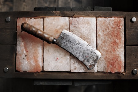 sal: cuchillo de carnicero de la vendimia en sal rosa del Himalaya. placas de sal. Barras de sal para cocinar. Imagen axe- cuchillo de cocina Foto de archivo