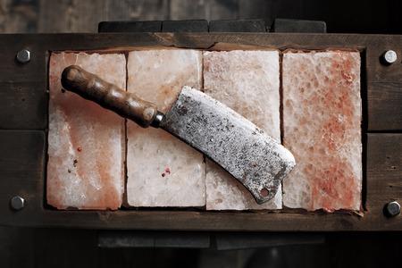 Vintage mes van het vlees op de Himalaya roze zout. Zout platen. Bars zout om te koken. Stock image axe- keukenmes Stockfoto