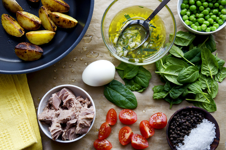 Fresh vegetables and ingredients for cooking tuna salad on the wooden. Dark colors. Foto de archivo