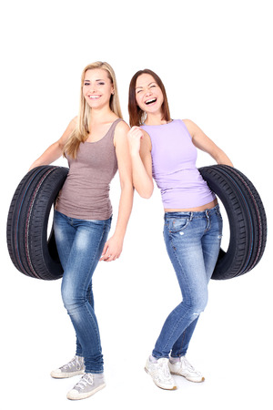 two persons only: Two women holding car wheels and laughing. Isolated on white.