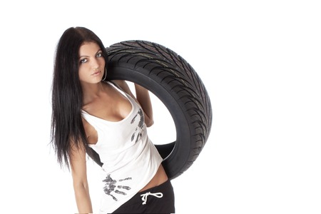 Young sexy girl holding a car wheel, isolated on white. Imagens