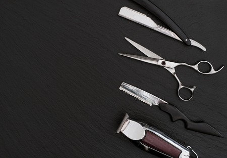 hair clippers: Barber shop equipment on Black background with place for text.  Professional hairdressing tools. Comb, scissor, clippers and hair trimmer isolated.