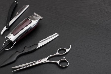 barber: Barber shop equipment on Black background with place for text.  Professional hairdressing tools. Comb, scissor, clippers and hair trimmer isolated.