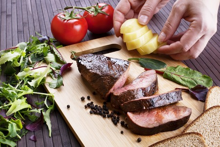 medium closeup: Close-up of Medium Rare Roast Beef with Fresh Herbs and  Vegetables Stock Photo