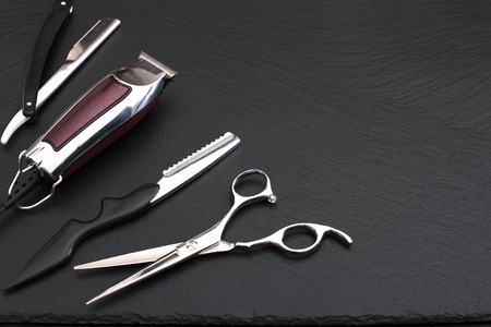 equipment: Barber shop equipment on Black background with place for text.  Professional hairdressing tools. Comb, scissor, clippers and hair trimmer isolated.