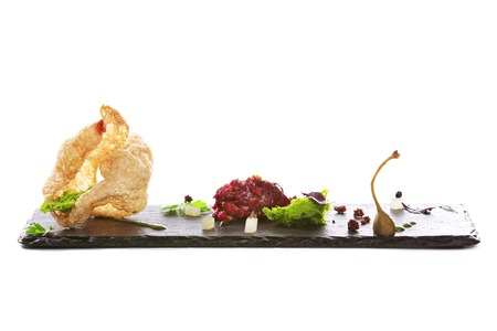 avant: Molecular modern cuisine. Chips Pigskin with tartare or carpaccio of beef. Stock image. Isolated on white.