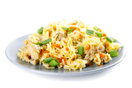 Geurige Pilau-pilavpilaf pilau, gebraden rijst met vlees en groenten op een grijze plaat. Geïsoleerd op wit. Macro. Stockfoto