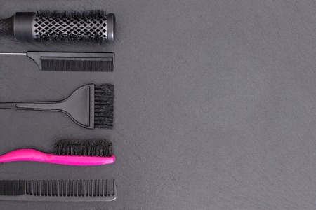 salon background: Salon Hairdresser Accessories, pink Comb, application brush,  brashing for cutting hair or colored on a black background Stock Photo