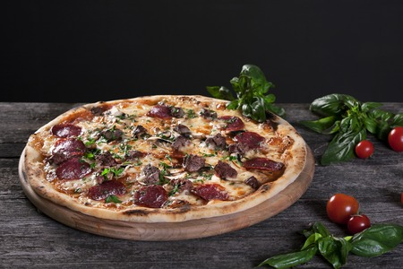 red onions: Pepperoni Pizza with salami, mushrooms , meat , beef, cheese  and green onions on the wooden background. Top view.