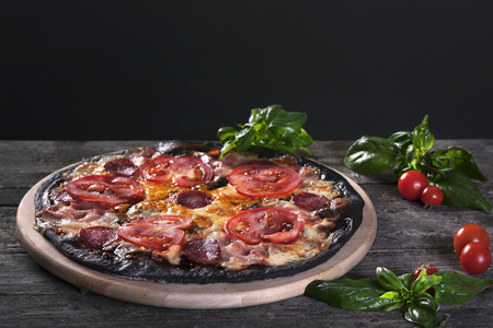 pizza base: Black pizza with salami, ham, tomato and cheese. Base with cuttlefish ink.