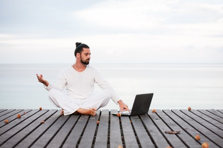 tailor seat: Caucasian man in white clothes meditating yoga with laptop on wooden pier