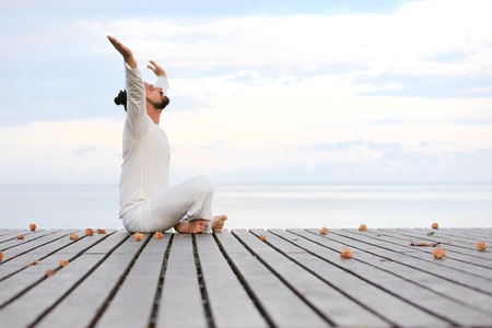 Caucasian man in white clothes meditating yoga with laptop on wooden pier