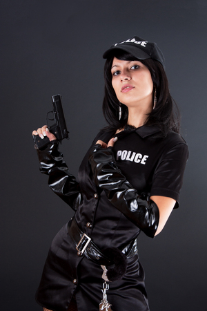 Portret of beautiful sexy policewoman with handcuffs in a black uniform that aiming a gun. Iisolated on black.