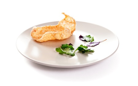 Molecular modern cuisine. Chips Pigskin on plate. Stock image. Isolated on white. Stock Photo