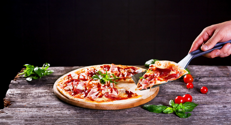Delicious fresh Pizza with bacon and tomato paste on the wooden background. Top view.