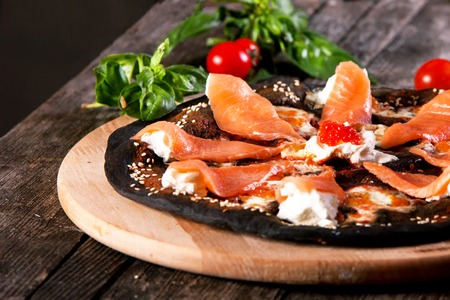 pizza base: Black pizza with red fish salmon and cream cheese . Base with cuttlefish ink.