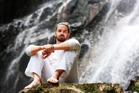 waterfall model: Man sitting in meditation yoga on rock at waterfall in tropical