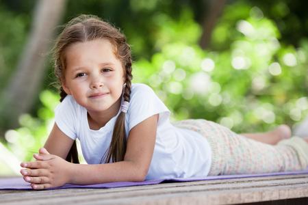Kind tun Übung auf der Plattform im Freien. Gesunder Lebensstil. Yoga Mädchen