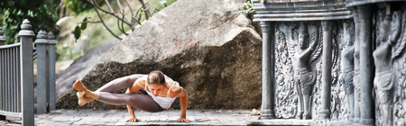 Young woman doing yoga in abandoned temple on wooden platform. Practicing. Stock Photo