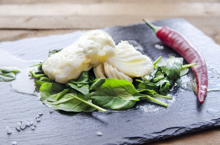 alaska pollock: White fish fillet with chili on fried spinach. Gray background. Stock Photo