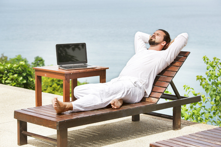 Businessman wearing white using laptop on the beach