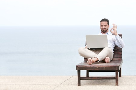 Businessman freelance on beach with laptop