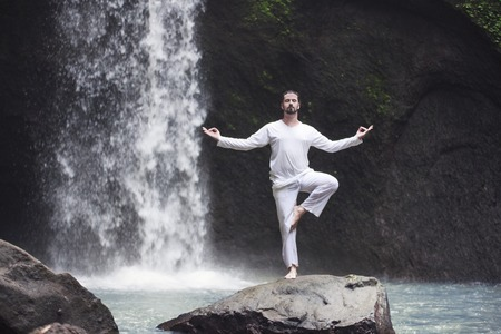Man standing in meditation yoga on rock at waterfall Banque d'images