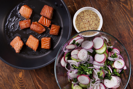 Grilled salmon with radish and spinach, served on wooden table. View from above, top studio shot