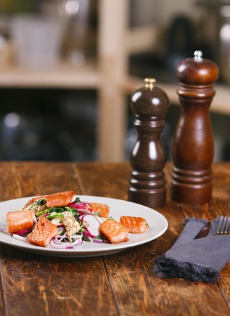 Grilled salmon with radish and spinach, served on white plate. View from above, top studio shot