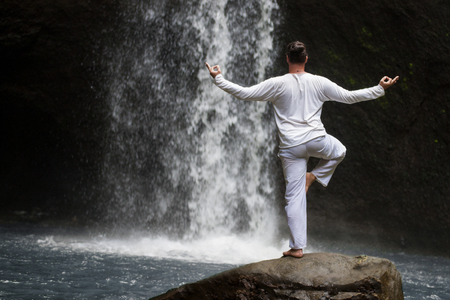Man standing in meditation yoga on rock at waterfall Stock Photo