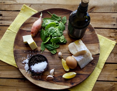 Fish, spinach and egg salad on a dark background, top view. Delicious healthy food concept