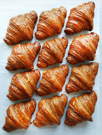Flat lay composition with tasty croissants on patterned background.