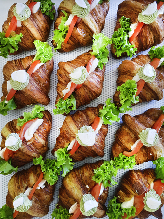 Breakfast sandwiches with mini croissants, smoked salmon slices and parsley on patterned background. Croissants with red fish