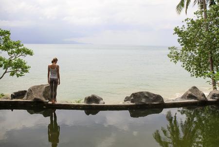 Woman practicing morning meditation Yoga at the beach