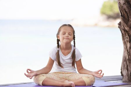 Child doing exercise on platform outdoors. Healthy lifestyle. Yoga girl