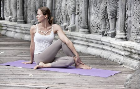 Woman doing yoga in abandoned temple. Outdoore Stock Photo