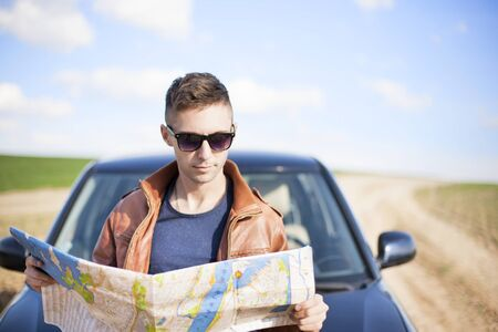 A tourist man next to the car looks at the map of the area. Traveler