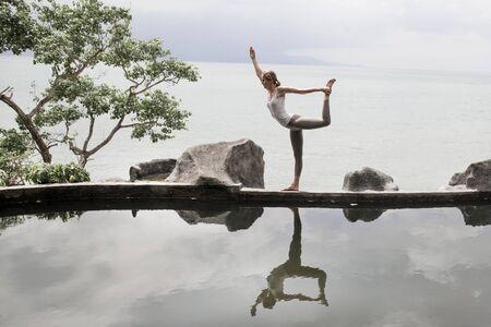Silhouette of a beautiful young woman practicing yoga in front of the lake at sunrise. Stock Photo