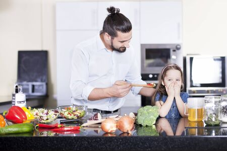 Little girl refusing to eat a salad while cooking and having lunch together in the kitchen