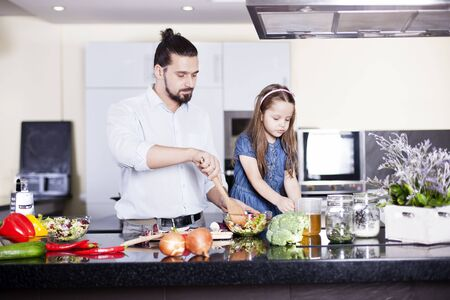 Father and daughter cooking meal together Foto de archivo