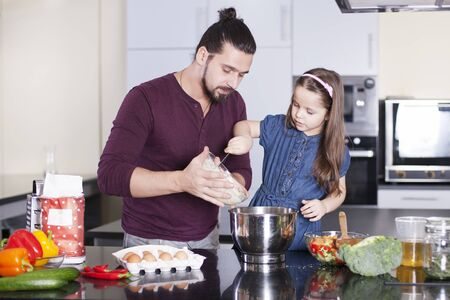 Father and daughter making meal together in kitchen. Cooking classes concept Foto de archivo