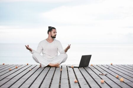 Man in white clothes meditating yoga on wooden pier