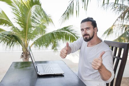 Vacation and technology. Work and travel. Young bearded man using laptop computer while sitting at beach cafe bar and showing thumbs up Foto de archivo