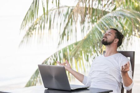Vacation and technology. Work and travel. Young bearded man using laptop computer while sitting at beach cafe bar.