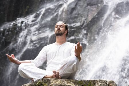 Wellness yoga meditation concept. Young man sitting in lotus position on the rock under tropical waterfall. Foto de archivo