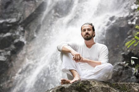 Wellness yoga meditation concept. Young man sitting in lotus position on the rock under tropical waterfall. Stock Photo