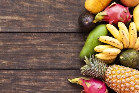 Tropical fruits, papaya, Dragon Fruit, rambutan, tamarind, avocado, granadilla, carambola kumquat mango mangosteen passionfruit On a wooden background. Assorted