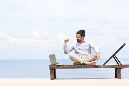 Young businessman on the beach resting on his deck chair using his tablet